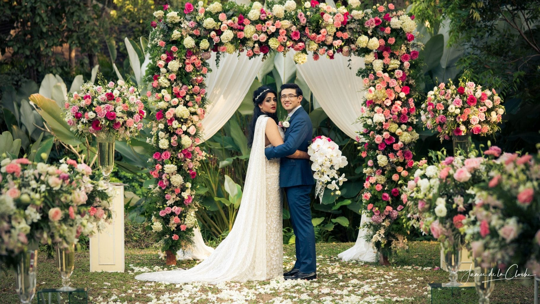 Bride, Groom and a Beautiful Flower Arch