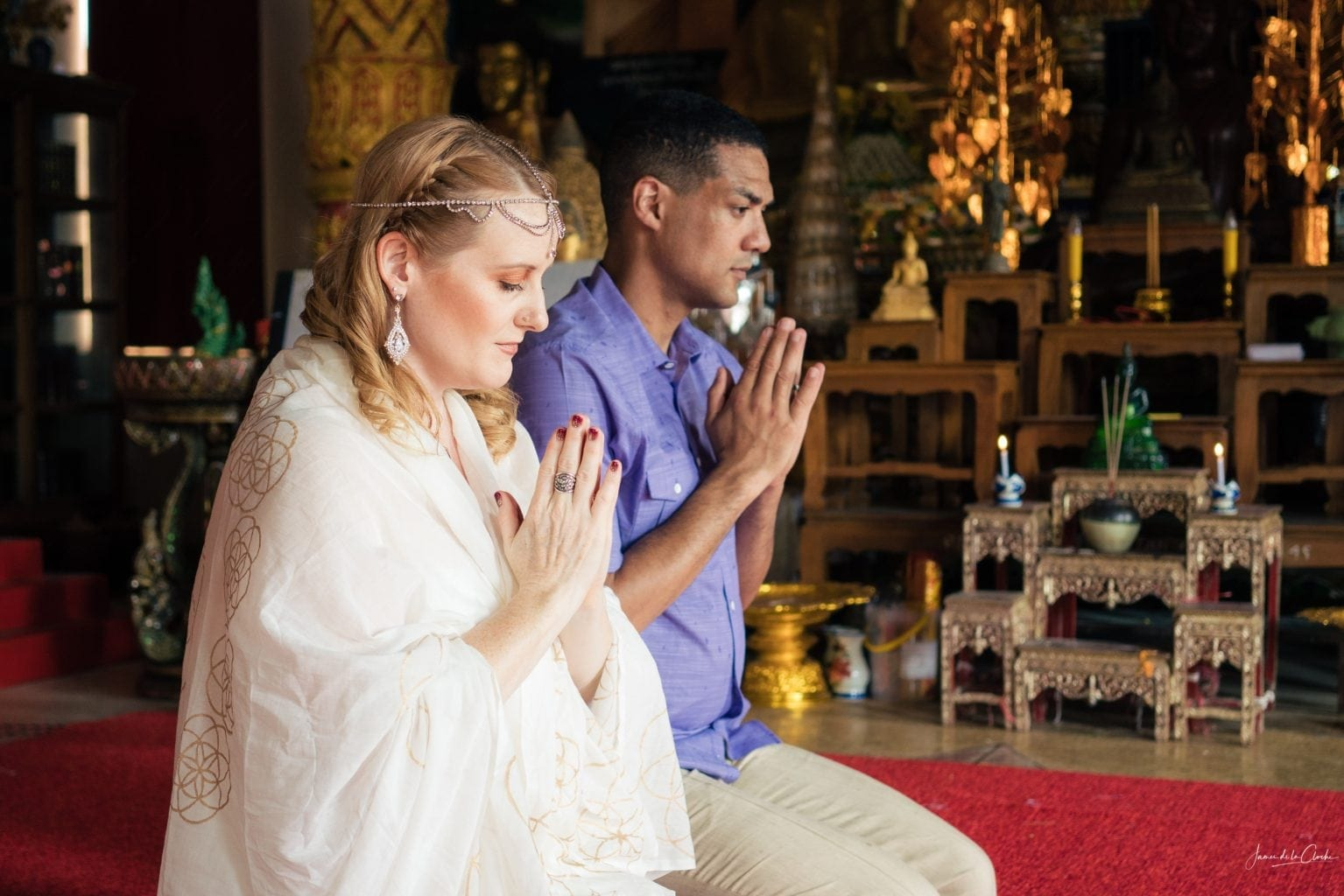 wedding couple hands raised in prayer at Buddhist temple