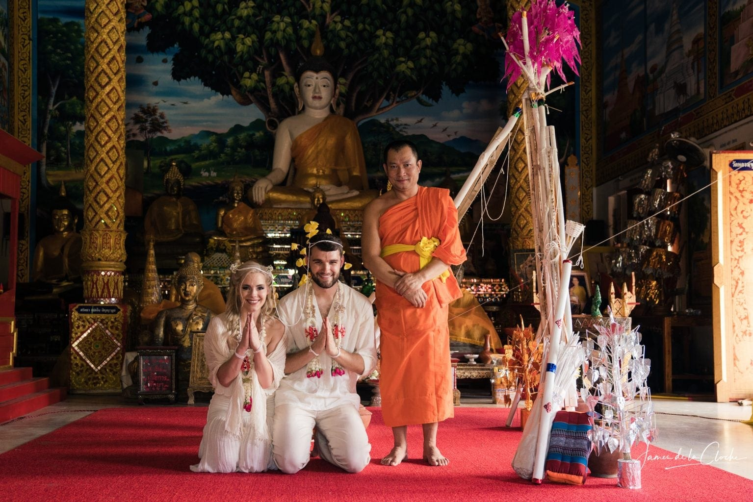 The monk and the couple pose in front of the Buddha